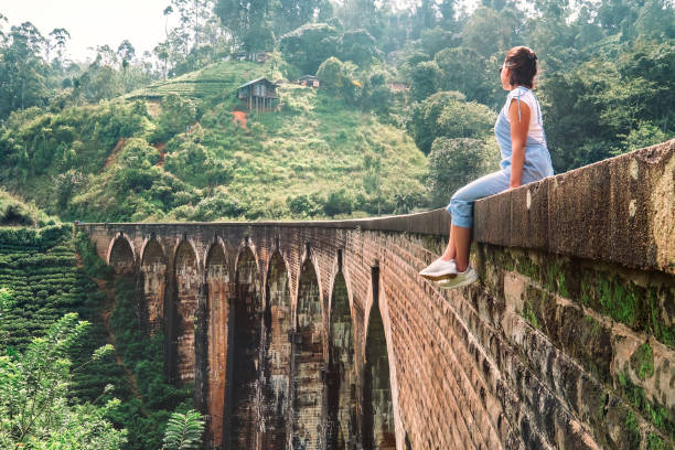 Woman sits on the Demodara nine arches bridge the most visited sight of Ella town in Sri Lanka stock photo