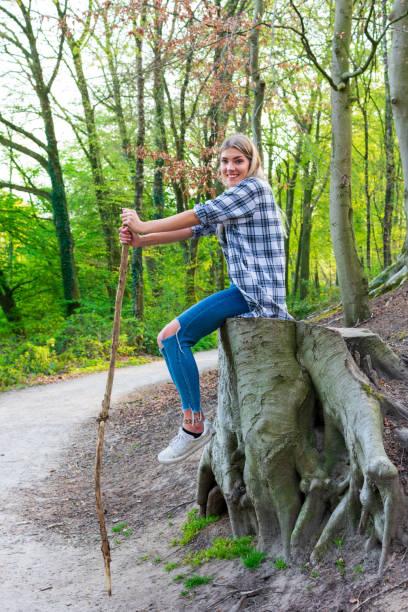 Frau sitzt lächelnd auf einem großen Baumstumpf im Wald. Ort: Deutschland, Nordrhein-Westfalen – Foto