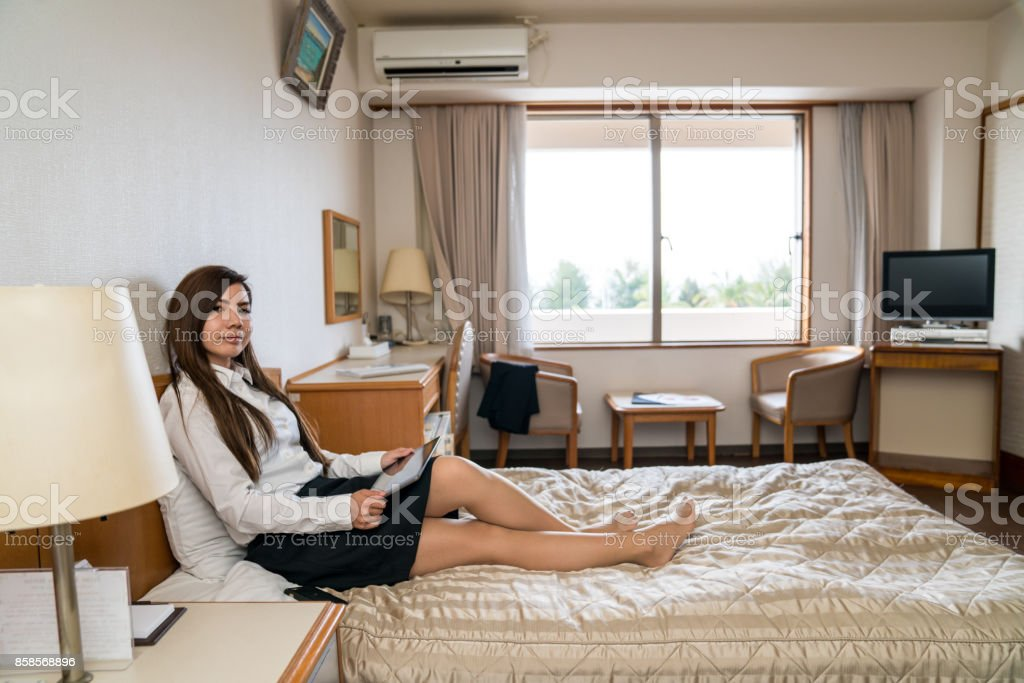 Woman sitting a bed inside a hotel room