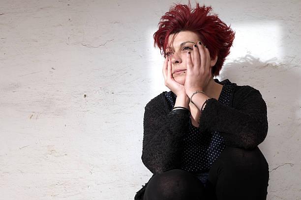 Frau sitzt vor weißer Wand – Foto