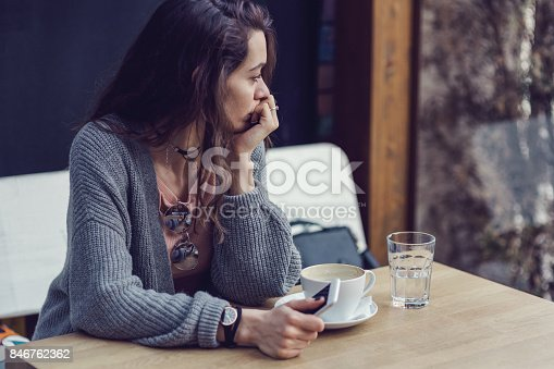 istock Woman sitting alone, having coffee and texting on her mobile phone 846762362