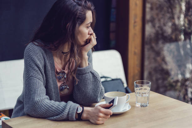 Woman sitting alone, having coffee and texting on her mobile phone Brunette female holding her mobile phone, looking through the window and drinking coffee one young woman only stock pictures, royalty-free photos & images