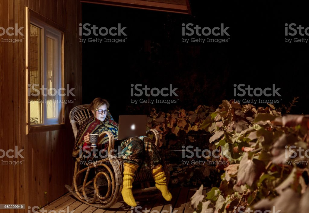 Woman sitting an rocking Chair with laptop computer stock photo