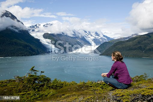 one adult woman in prince william sound alaska overlooking columbia glacier