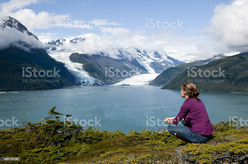 Woman sitting and gazing at water and snowy hills in Alaska stock photo