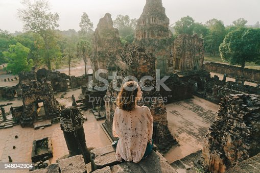 Young Caucasian woman  sitting  in Angkor Temple in  Siem Reap, Cambodia