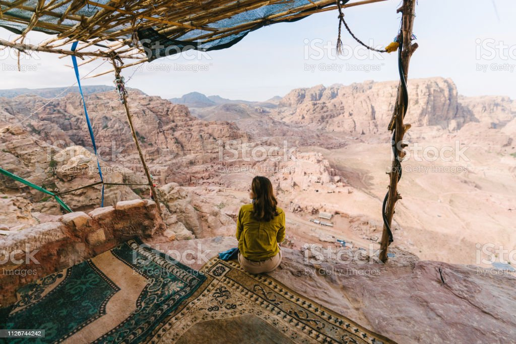 Woman sitting and looking at view of desert in Petra Young Caucasian woman sitting and looking at view of desert in Petra Adult Stock Photo
