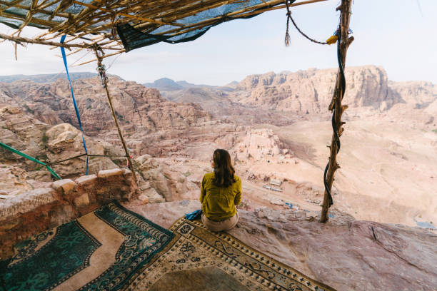 femme assise et regarder la vue du désert à petra - jordan photos et images de collection