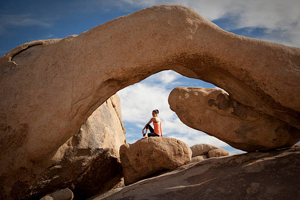 Woman sitting and practicing yoga under Arch Rock. stock photo