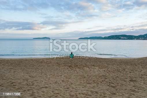 Woman sitting and thinking alone in the beach.