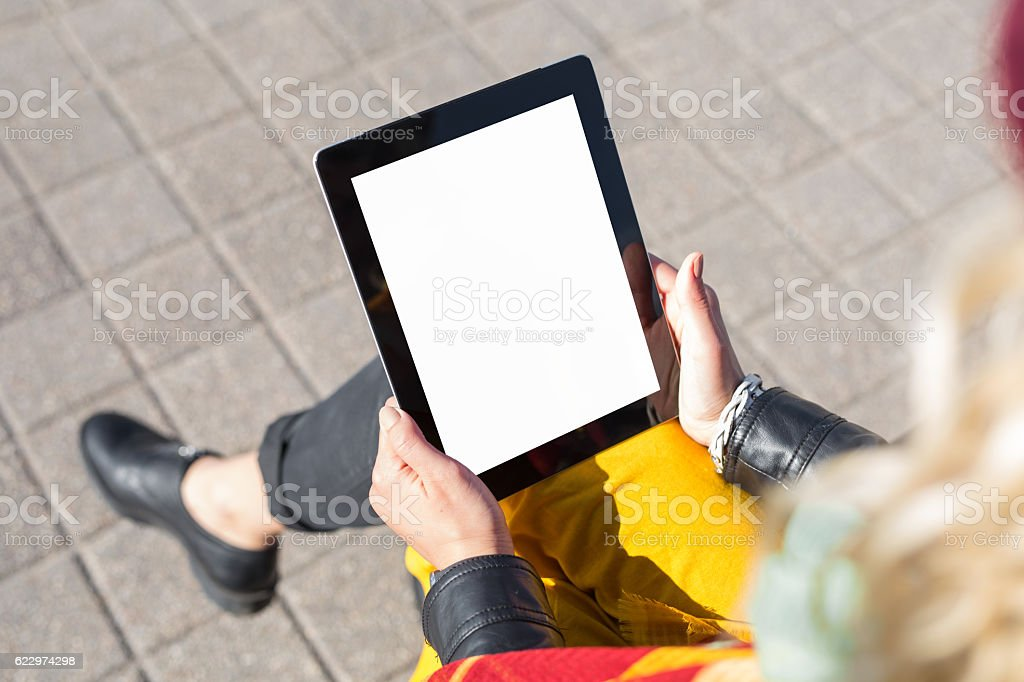 Woman sitting and using blank screen tablet stock photo