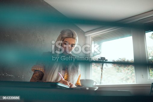 1183295518 istock photo Woman sitting and writing in the coffee bar indoors 964339686