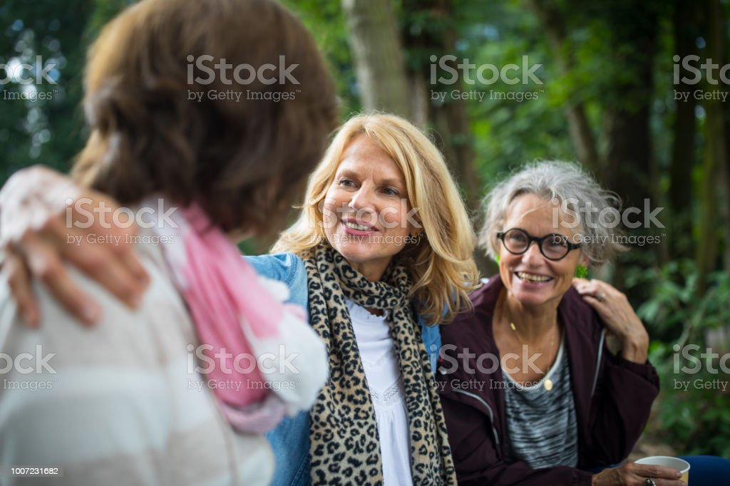 Woman sitting arms around friends at lakeshore stock photo