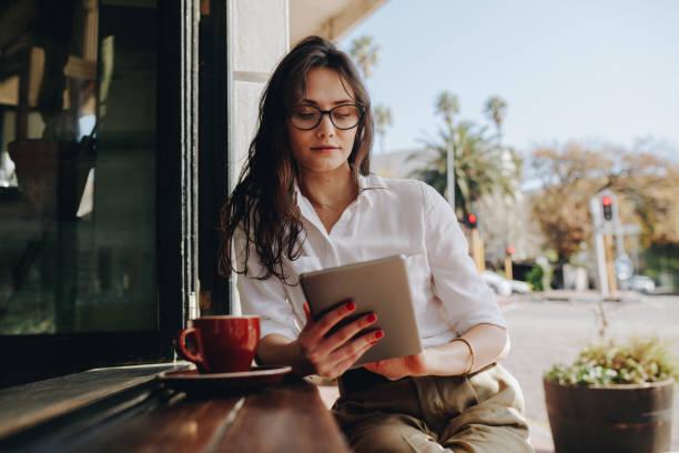 디지털 태블릿에 노력 하는 카페에 앉아 여자 - 디지털 태블릿 사용하기 뉴스 사진 이미지