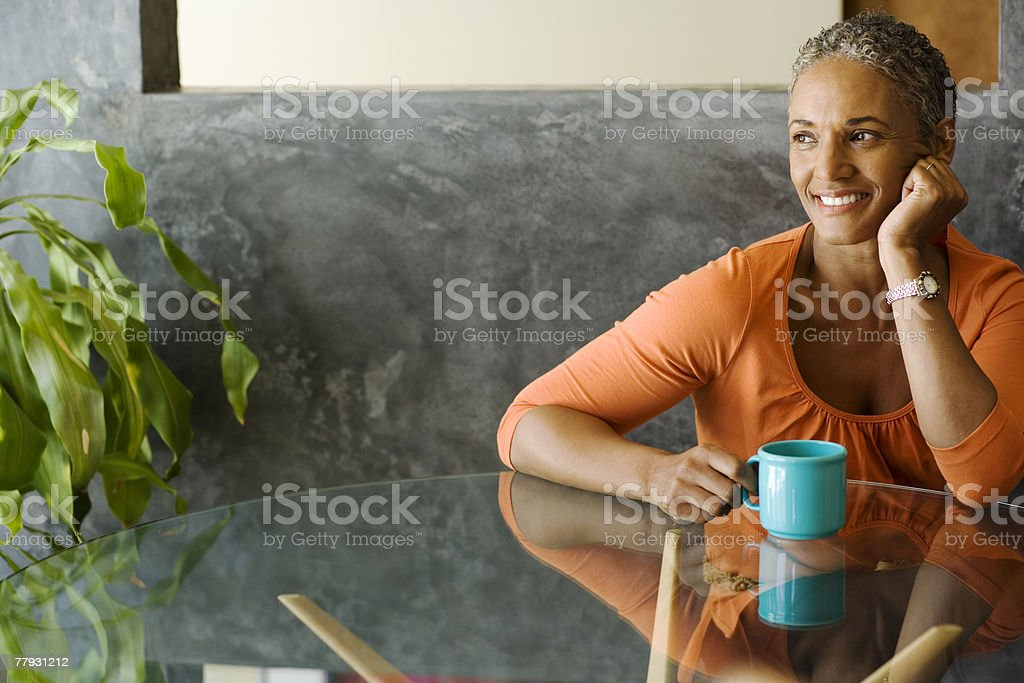 Woman sitting at a table with a mug smiling stock photo