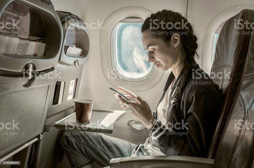 Woman sitting at airplane and looking to mobil phone. stock photo