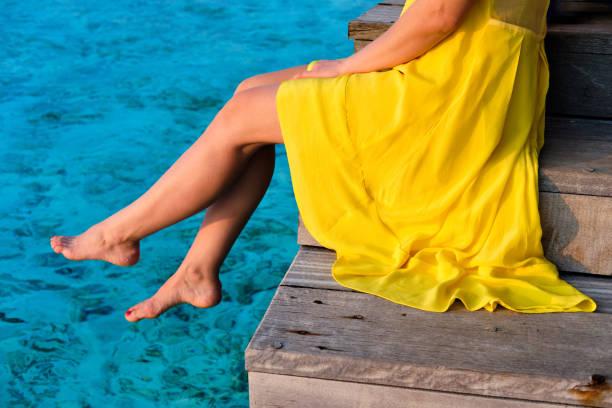 Frau sitzt am Strandsteg – Foto