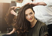 Happy woman sitting at beauty salon, making beautiful evening hairstyle with curls, copy space