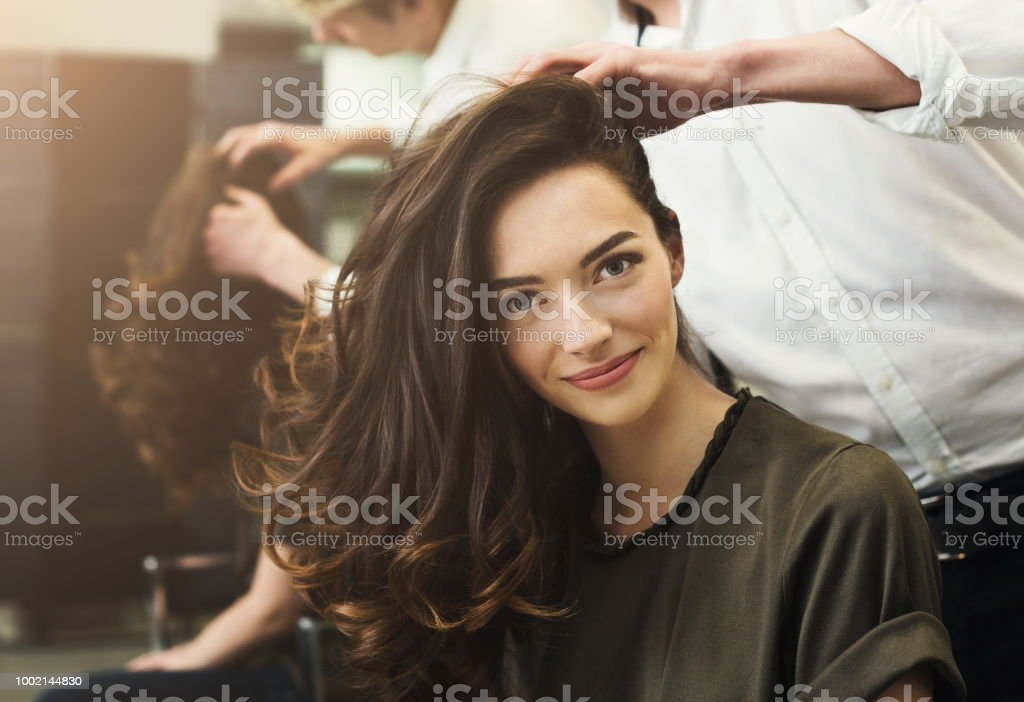 Woman sitting at beauty salon, making hairdo stock photo