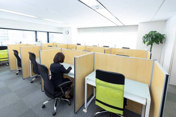 机の上に座って働く女性 ストックフォト