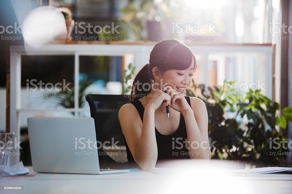 Woman sitting at desk looking at documents stock photo