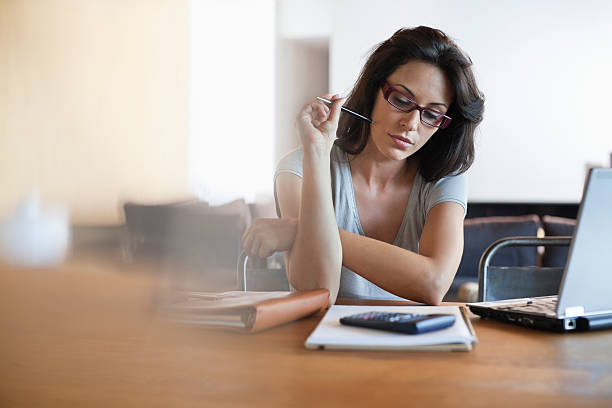 woman sitting at desk looking at notebook - home finances stock pictures, royalty-free photos & images