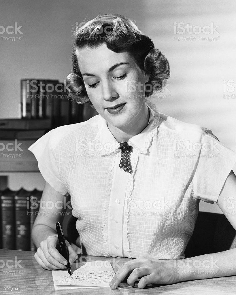 Женщина, сидящая на стол, написание Примечание Стоковые фото Стоковая фотография