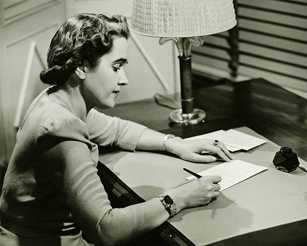 Woman sitting at desk, writing, (B&W)  20th century stock pictures, royalty-free photos & images