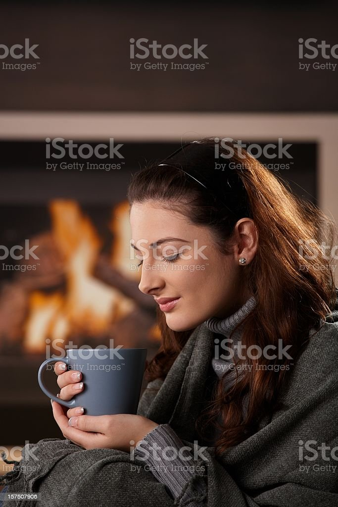 Woman sitting at fireplace royalty-free stock photo
