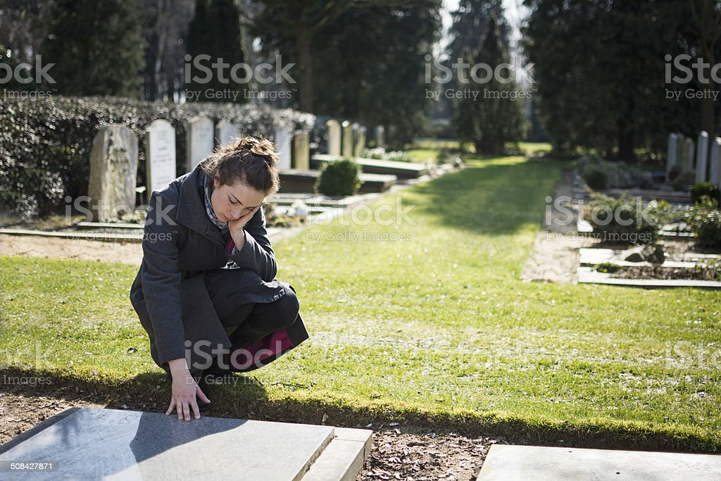 Woman sitting at grave stock photo