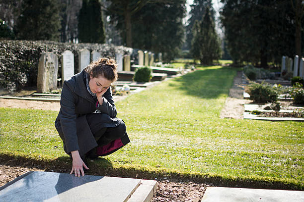 Woman sitting at grave Woman sitting at grave with hand on grave mourner stock pictures, royalty-free photos & images