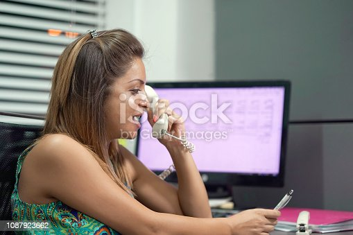 1167562098 istock photo Woman sitting at her desk working and answering a phone call. 1087923662