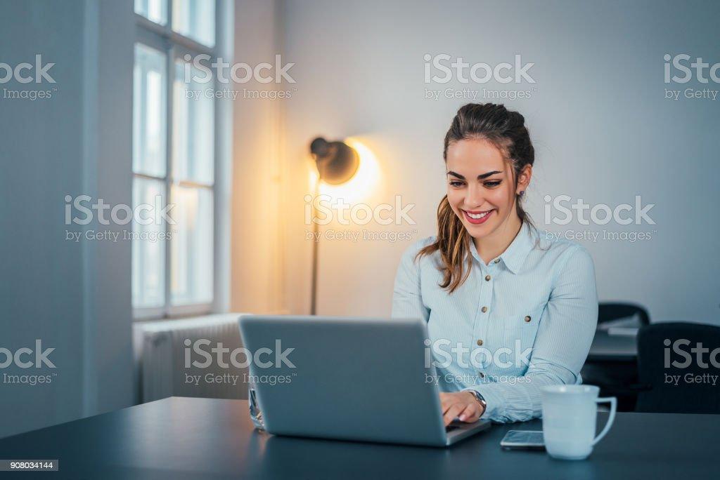 Frau an ihrem Arbeitsplatz im Büro sitzen und arbeiten per Notebook. – Foto