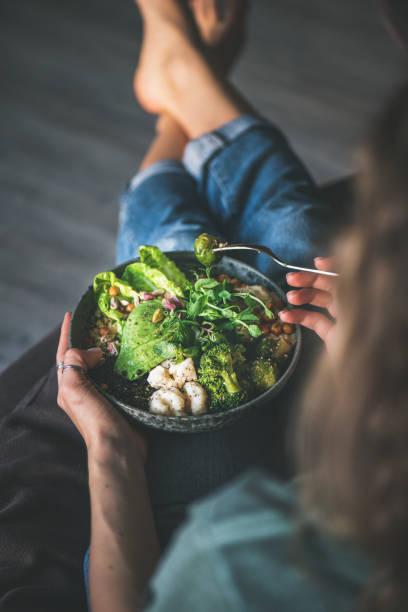 kobieta siedząca w domu i jedząca wegańską grę o mistrzostwo - jedzenie wegetariańskie zdjęcia i obrazy z banku zdjęć