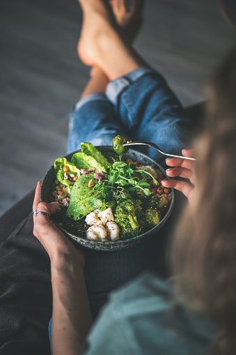 istock Woman sitting at home and eating vegan superbowl 1139470588