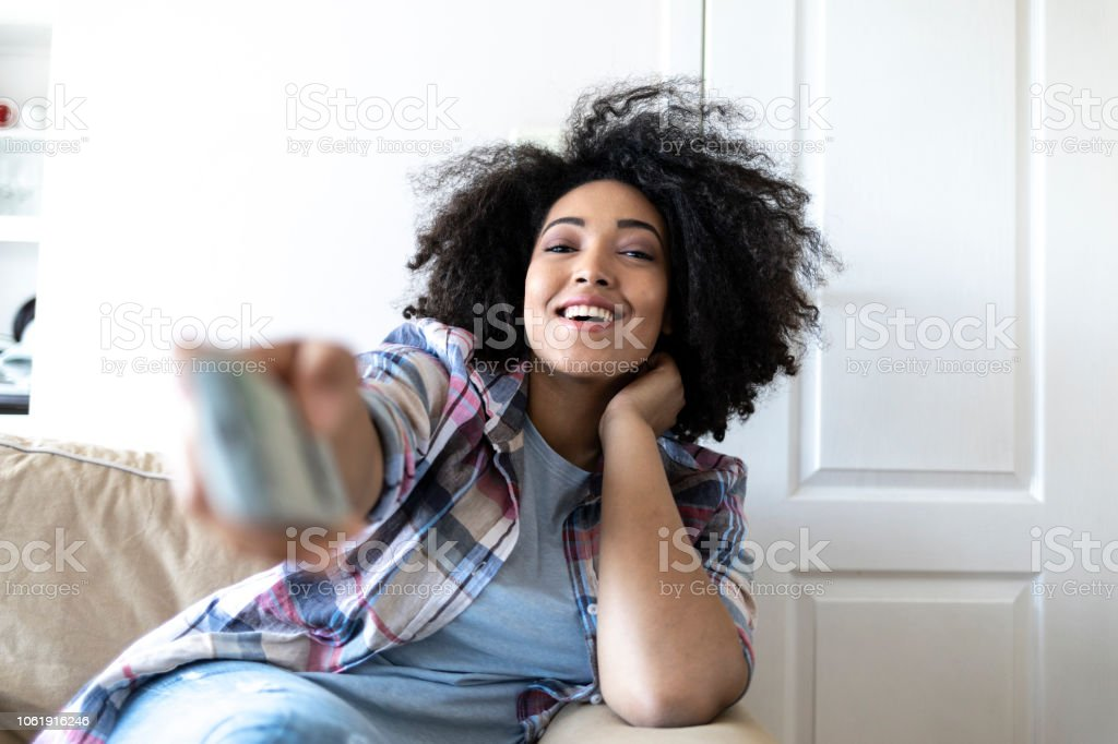 Woman sitting at home and watching TV, holding remote controller.