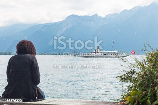 Woman sitting at Montreux promenade and enjoying views of Lake Geneva (Lac Leman) and traditional paddle steamboat Montreux cruising along Swiss shore, Vaud, Switzerland