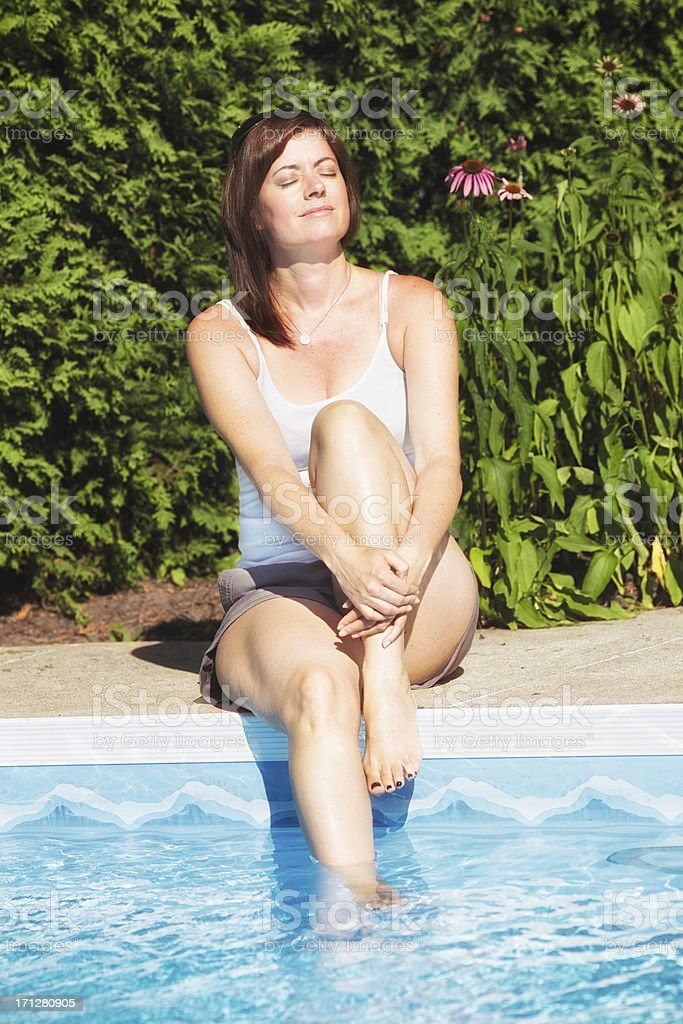 Woman sitting at pool soaking up the sun royalty-free stock photo