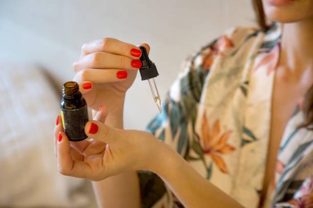 Frau sitzt im Spa-Center und wählt ätherisches Öl für die Behandlung – Foto