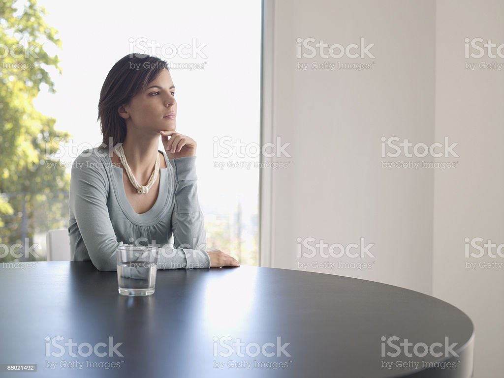 Femme assise à table à la rêverie photo libre de droits
