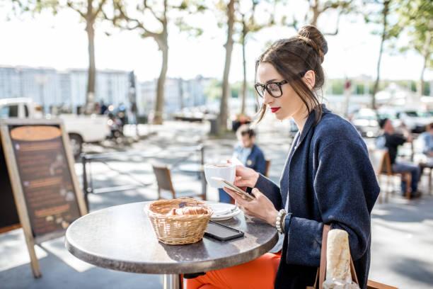 femme assise à l'extérieur du café - mode paris photos et images de collection