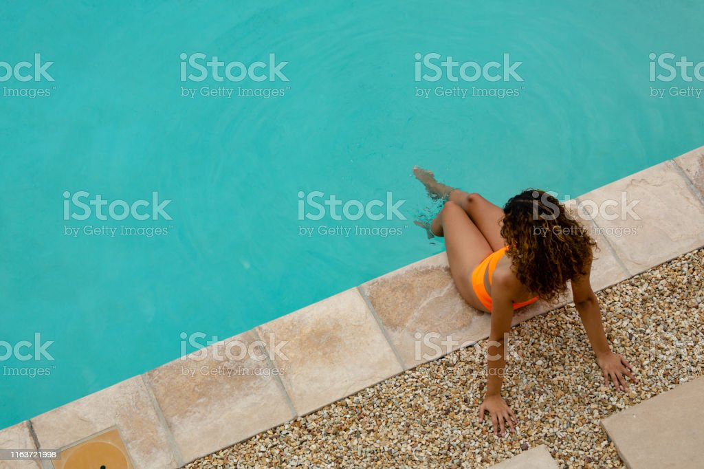 High angle view of mixed-race woman sitting at the edge of swimming...