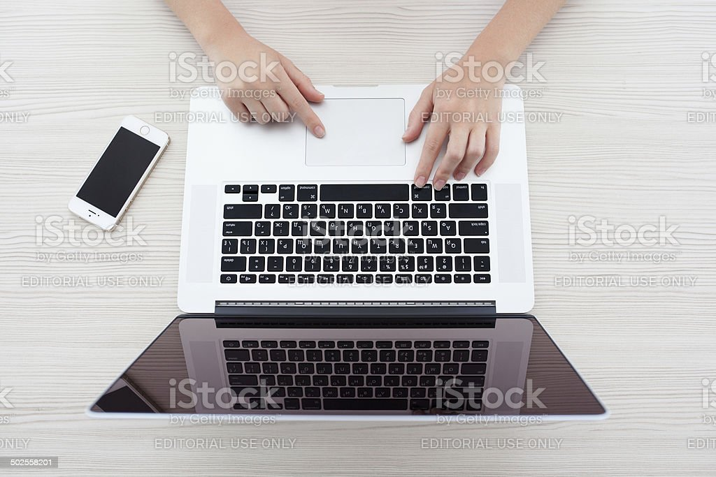 woman sitting at the MacBook Pro Retina and iPhone 5s stock photo