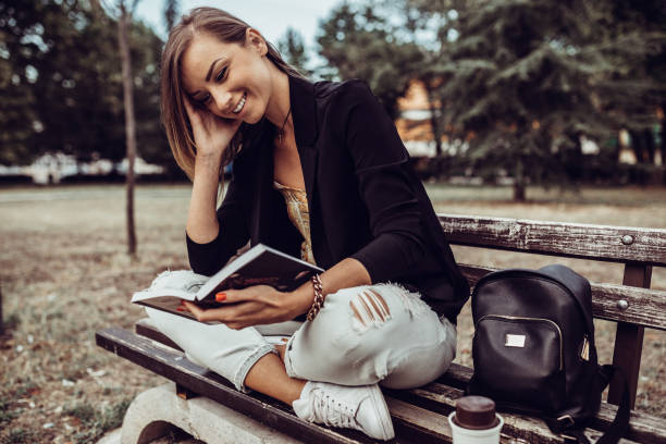 Woman sitting at the park bench and reading a book stock photo