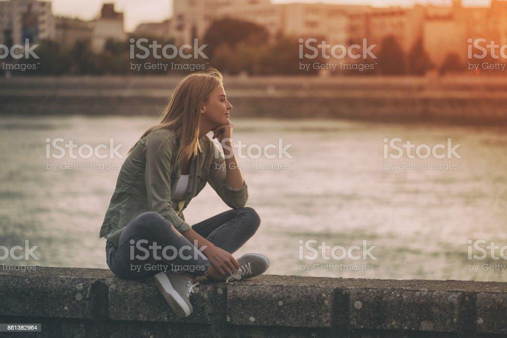 Frau sitzt am Ufer des Flusses – Foto