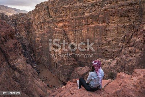 istock A woman sitting at viewpoint of Petra ancient city looking at the Treasury or Al-khazneh, Jordan, Arab 1213508059