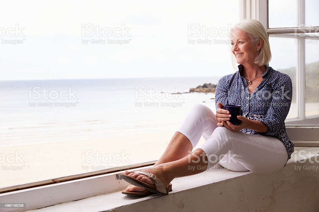 Woman Sitting At Window And Looking At Beautiful Beach View stock photo