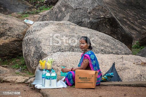 Mamallapuram, Tamil Nadu, India - August 2018: A candid portrait of an Indian woman selling mineral water and corn at a tourist site in Mahabalipuram.
