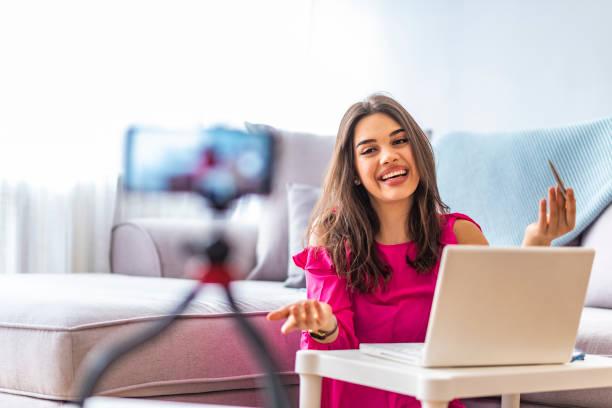 kvinna sitter bredvid skrivbord med laptop medan filma hennes sändning - video call bildbanksfoton och bilder