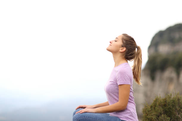 Woman sitting breathing fresh air in the mountain stock photo